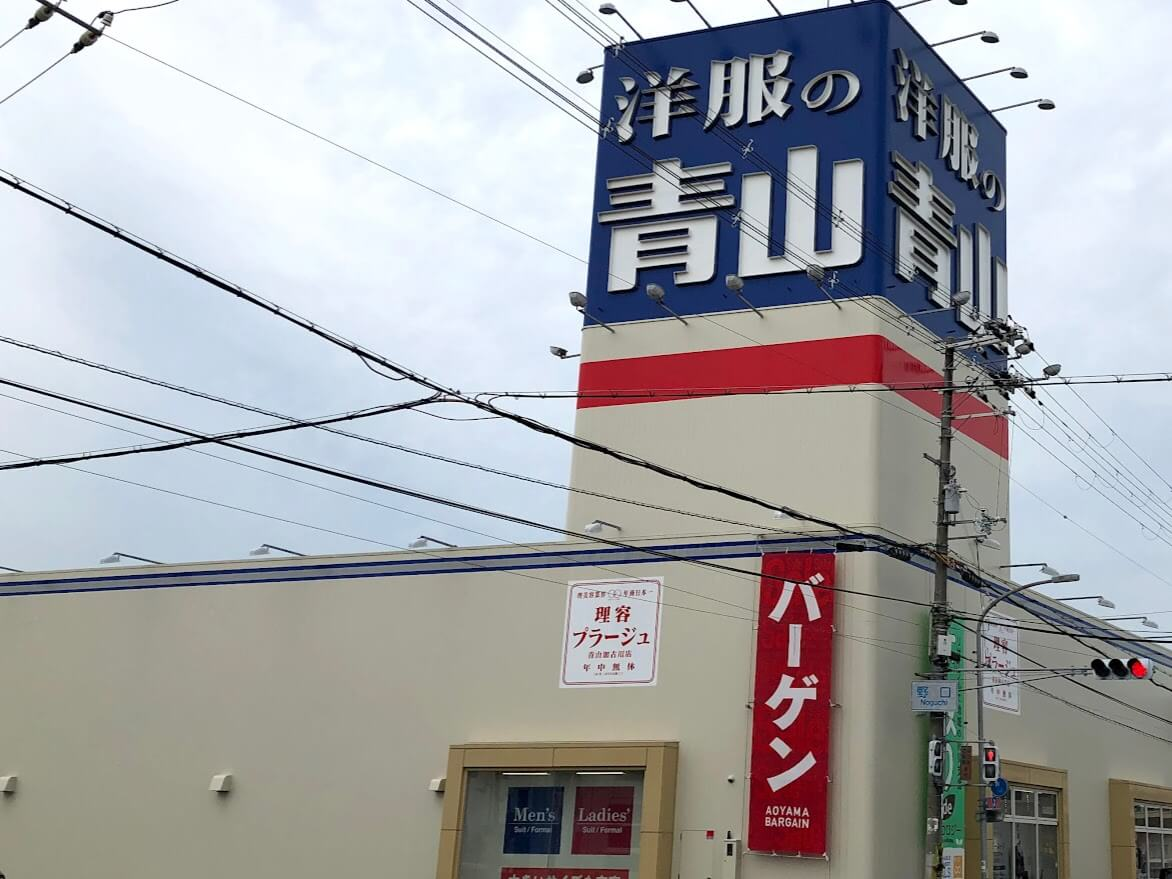 洋服の青山に付く理容プラージュ青山加古川店の看板